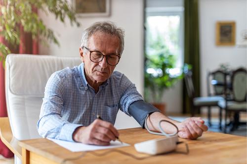 huber thomas marcelle_man taking blood pressure test medical device writing